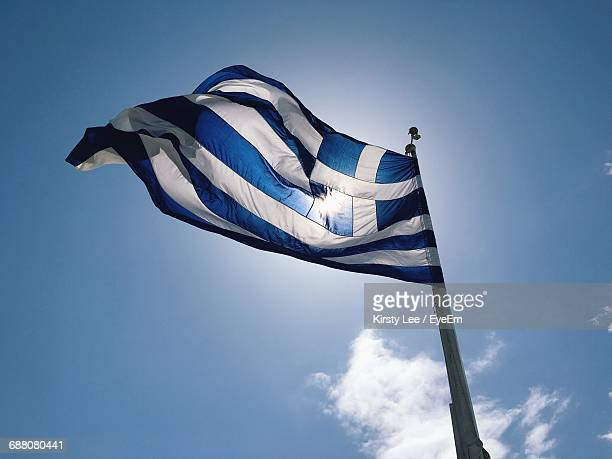 low angle view of flag against blue sky - greek flag stock pictures, royalty-free photos & images