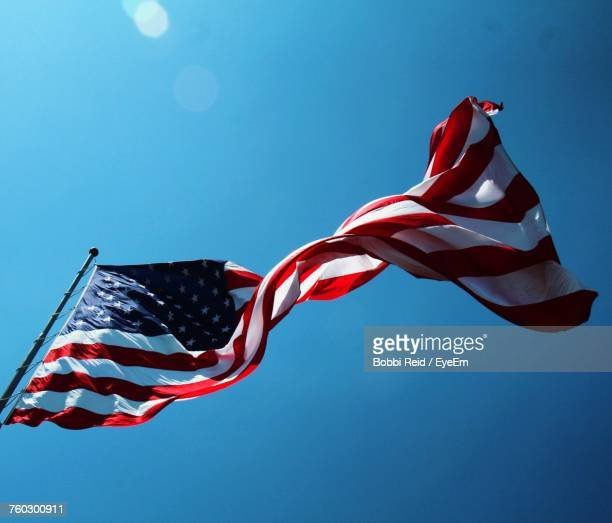 low angle view of flag against blue sky - verenigde staten stockfoto's en -beelden