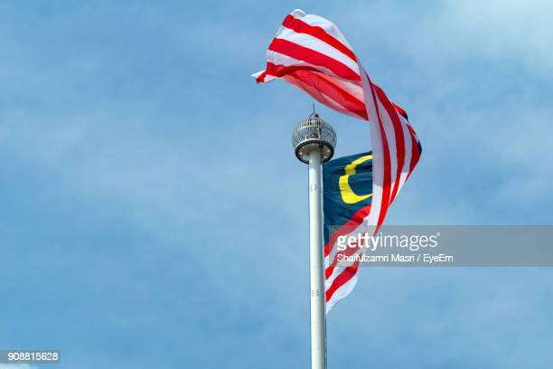 low angle view of flag against blue sky - shaifulzamri photos et images de collection