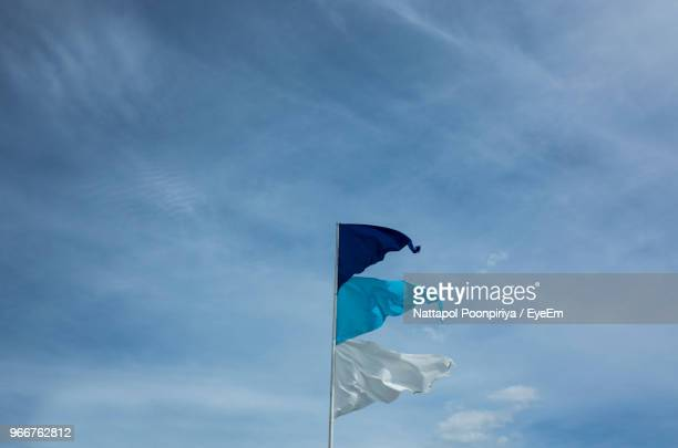 low angle view of flag against blue sky - 旗 ストックフォトと画像
