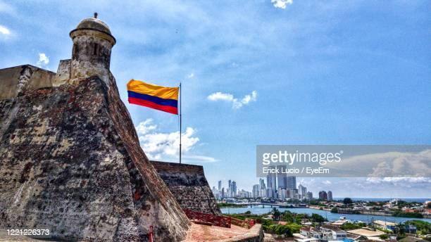 low angle view of flag against buildings in city - colombia foto e immagini stock