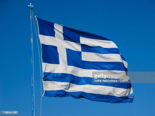 low angle view of flag against clear blue sky - greek flag stock pictures, royalty-free photos & images