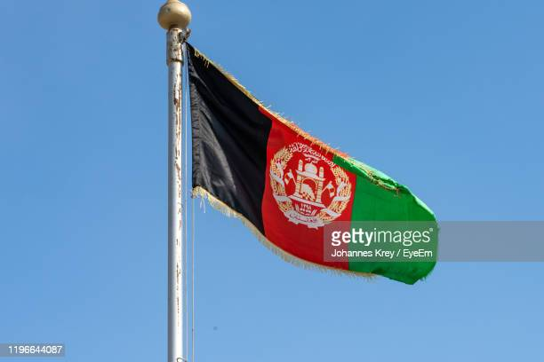 low angle view of flag against clear blue sky - afghanistan photos et images de collection