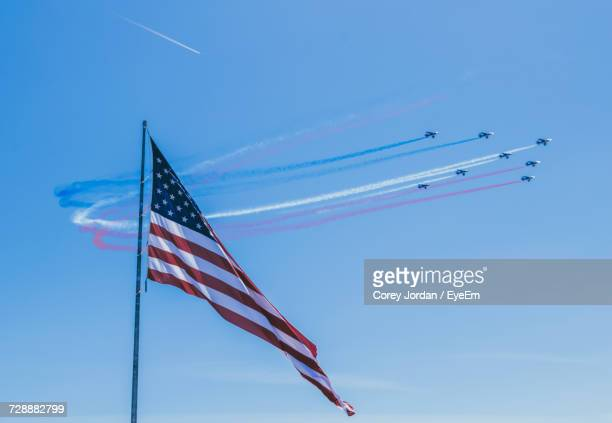 low angle view of flag against clear blue sky - independence day stock pictures, royalty-free photos & images