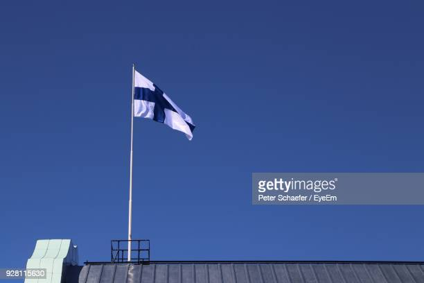 low angle view of flag against clear blue sky - finnish flag stock photos and pictures