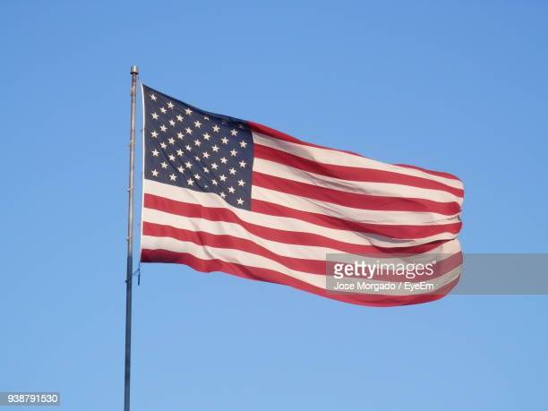 low angle view of flag against clear blue sky - flagpole stock pictures, royalty-free photos & images