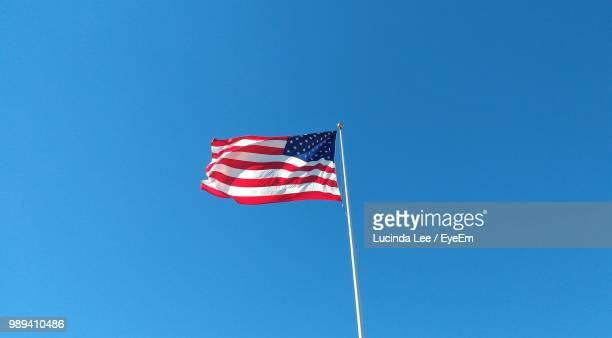 low angle view of flag against clear blue sky - stars and stripes stock pictures, royalty-free photos & images