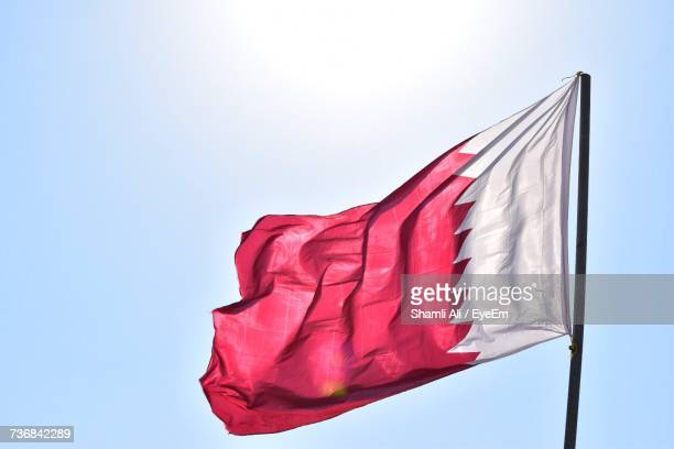 low angle view of flag against clear sky - qatar stock photos and pictures