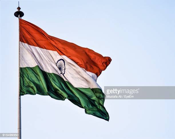 low angle view of flag against clear sky - indian flag stock pictures, royalty-free photos & images