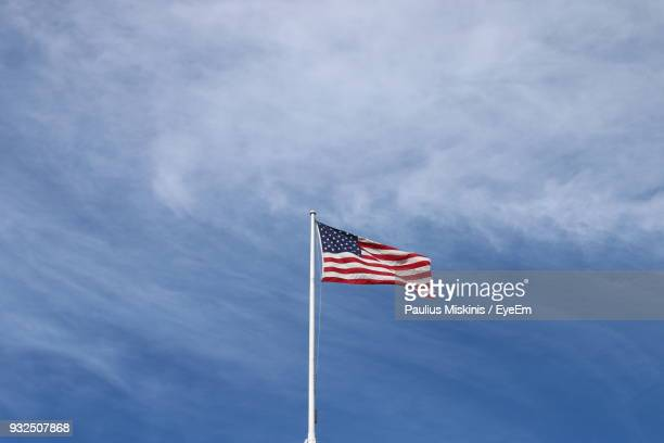 low angle view of flag against cloudy sky - flagpole stock pictures, royalty-free photos & images