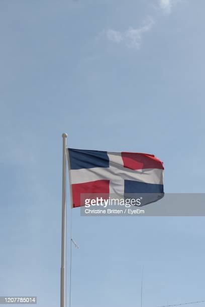 low angle view of flag against sky - dominican republic flag stock pictures, royalty-free photos & images