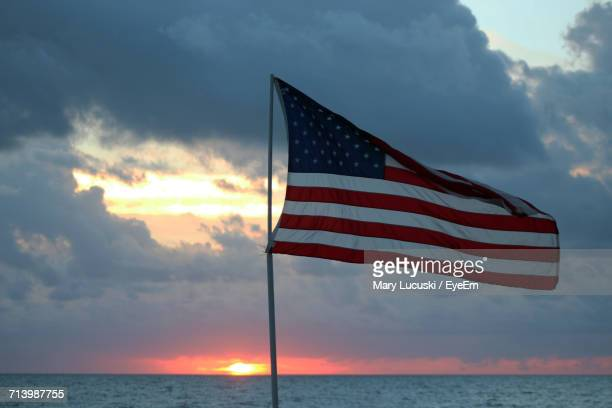 low angle view of flag against sky - american flag ocean stock pictures, royalty-free photos & images