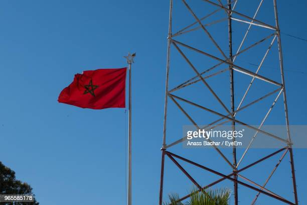 Low Angle View Of Flag By Electricity Pylon Against Blue Sky
