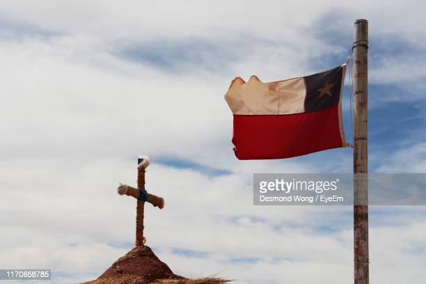 low angle view of flag by religious cross against sky - bandiera del cile foto e immagini stock