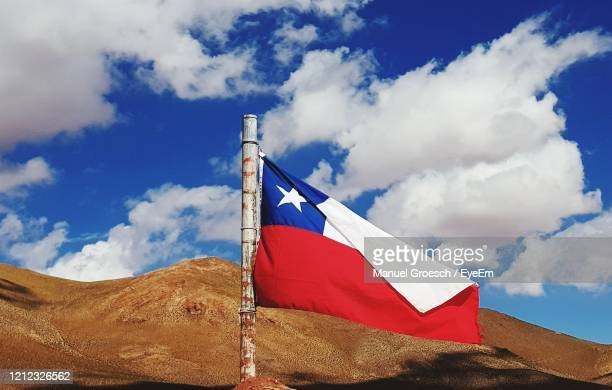 low angle view of flag of chile on mountain against blue cloudy sky - bandiera del cile foto e immagini stock