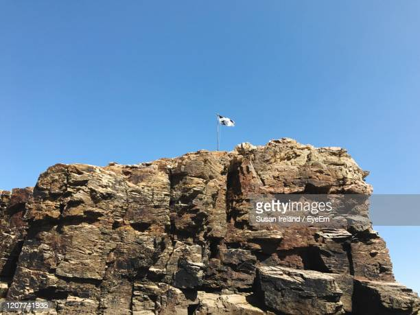 low angle view of flag on cliff against clear blue sky - cornish flag stock pictures, royalty-free photos & images