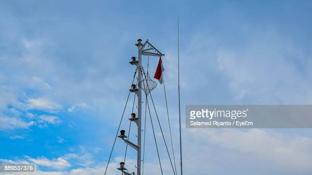 Low Angle View Of Flag On Mast Against Blue Sky