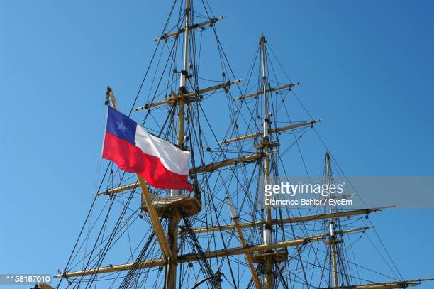 low angle view of flag on masts against clear blue sky - bandiera del cile foto e immagini stock