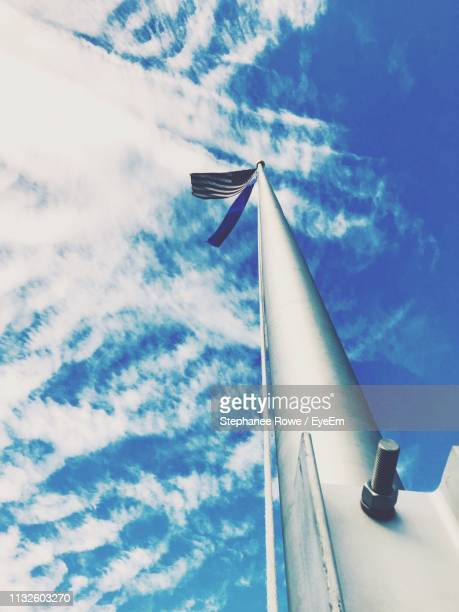 low angle view of flag pole against blue sky - flagpole stock pictures, royalty-free photos & images