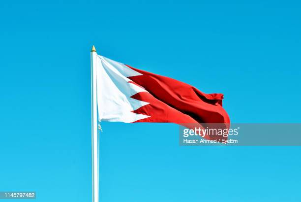 low angle view of flag waving against clear blue sky - bahrain stock-fotos und bilder