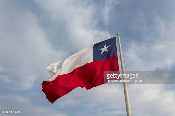 low angle view of flag waving against cloudy sky - chile stock pictures, royalty-free photos & images