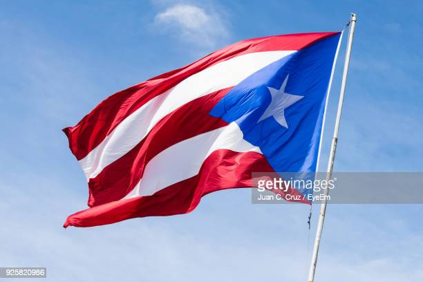 low angle view of flag waving against sky - puerto rico stock pictures, royalty-free photos & images