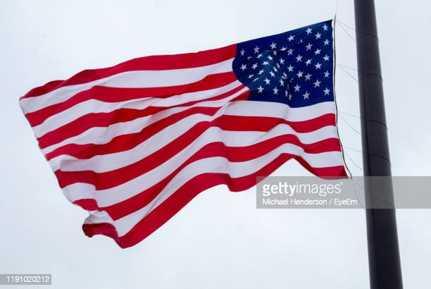 low angle view of flag waving on pole against clear sky - ウィスコンシン州シボイガン ストックフォトと画像