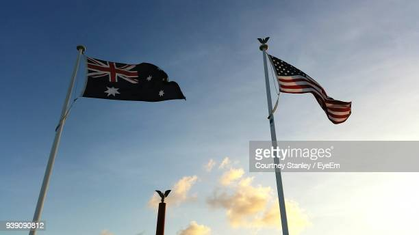 low angle view of flags against blue sky - australian flag stock pictures, royalty-free photos & images