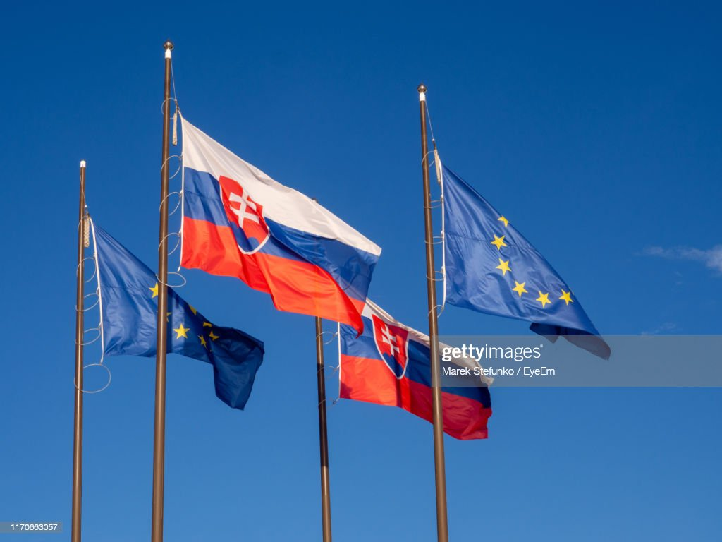 Low Angle View Of Flags Against Clear Blue Sky : Stock Photo