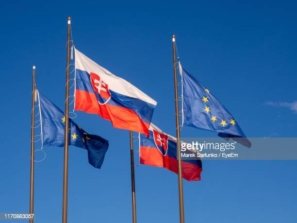 low angle view of flags against clear blue sky - marek stefunko stock photos and pictures