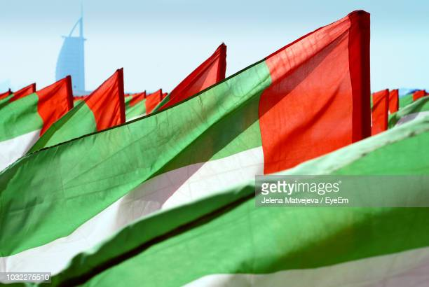 low angle view of flags against sky - gulf countries stock pictures, royalty-free photos & images