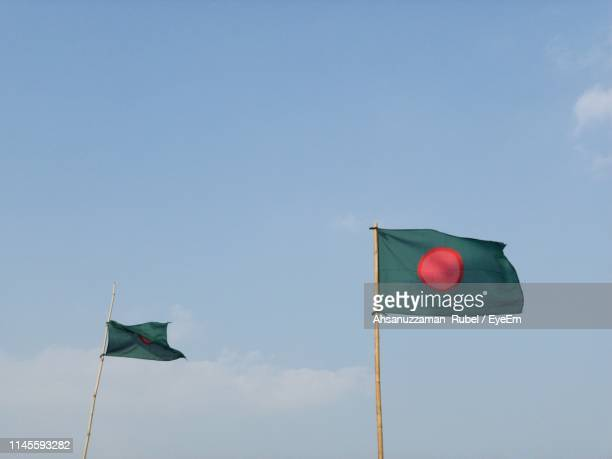 low angle view of flags against sky - bangladesh flag stock photos and pictures