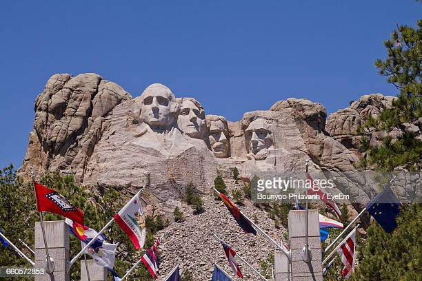 Low Angle View Of Flags At Mt Rushmore National Monument Against Clear Sky