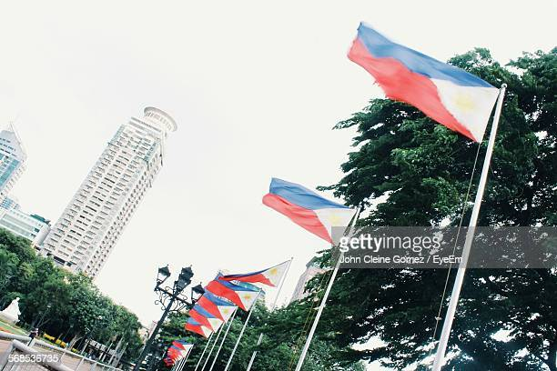 low angle view of flags in rizal park against clear sky - philippines flag stock pictures, royalty-free photos & images