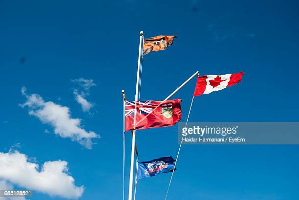 Low Angle View Of Flags On Mast Against Sky