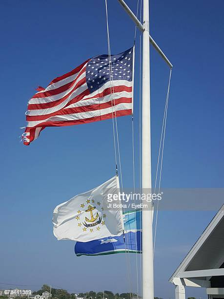 Low Angle View Of Flags On Pole Against Blue Sky