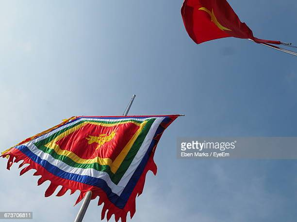 Low Angle View Of Flags Outside Ngoc Son Temple Against Blue Sky