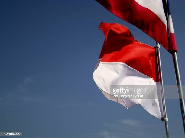 low angle view of flags waving against blue sky - indonesia flag stock photos and pictures
