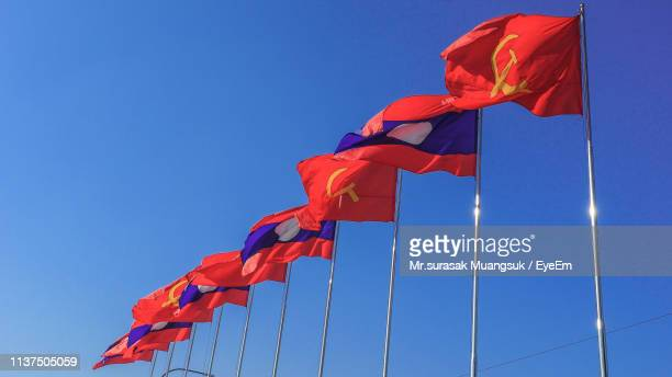 low angle view of flags waving against clear blue sky - bandiera comunista foto e immagini stock