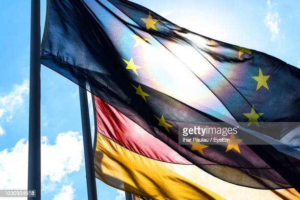 low angle view of flags waving against sky during sunny day - europe stock-fotos und bilder