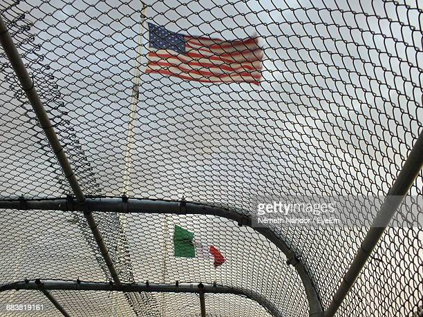 low angle view of flags waving seen through chainlink fence - ciudad juarez stock pictures, royalty-free photos & images