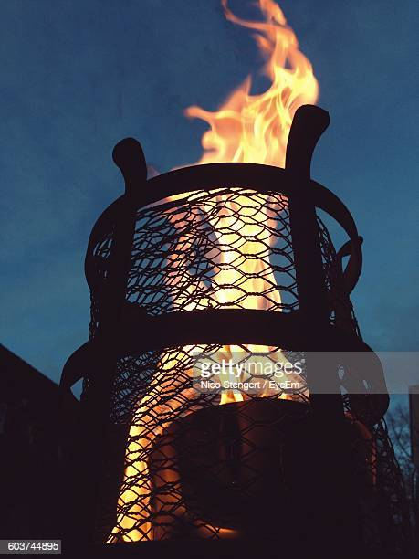 low angle view of flaming torch against sky at dusk - 聖火トーチ ストックフォトと画像