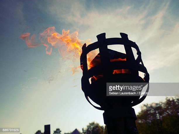 Low Angle View Of Flaming Torch Against Sky