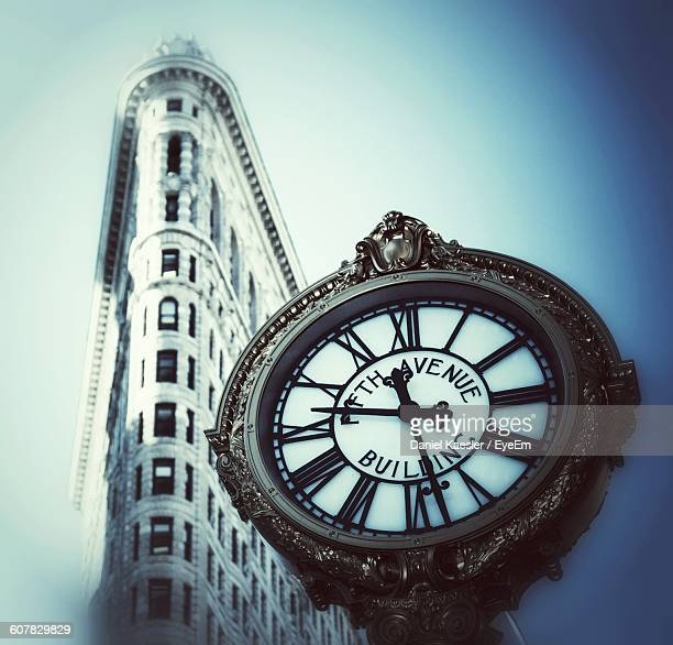 Low Angle View Of Flatiron Building And Wall Clock