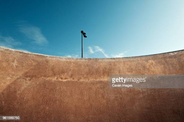 low angle view of floodlight on sports ramp against sky - skateboard park stock pictures, royalty-free photos & images