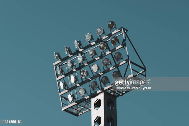 low angle view of floodlights against clear blue sky - stadium lights stock pictures, royalty-free photos & images