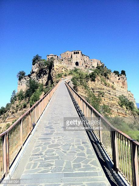 low angle view of footpath towards civita di bagnoregio against clear blue sky - civita di bagnoregio foto e immagini stock