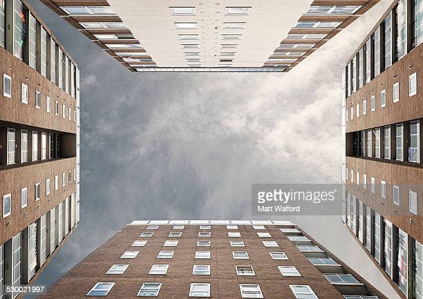 low angle view of four apartment block exteriors face to face - claustrofobia fotografías e imágenes de stock