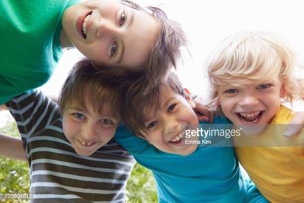 low angle view of four boys with arms around each other in park - only boys stock photos and pictures