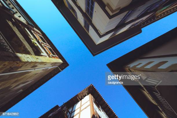 low angle view of four buildings from a crossroad - cross shape stock pictures, royalty-free photos & images